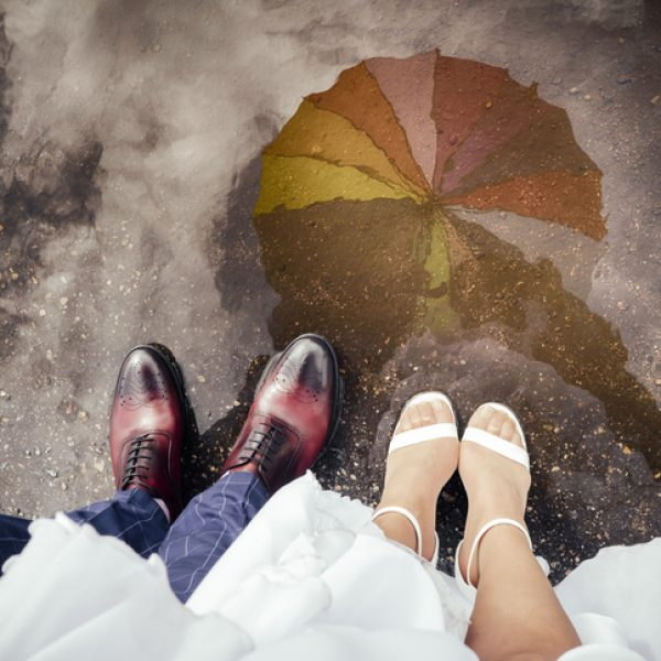 The bride and groom standing in the puddle, colorful umbrella visible in the reflection.
